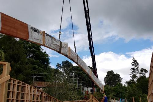 Lifting 15m curved glulam beam down driveway and into building at Clevedon