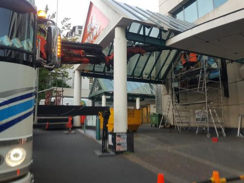 Removing Real Groovy sign under canopy in Queen St, Auckland CBD
